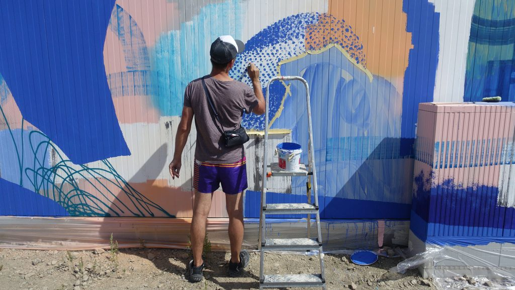 Ino is finishing a mural that Marc Southwell helped with