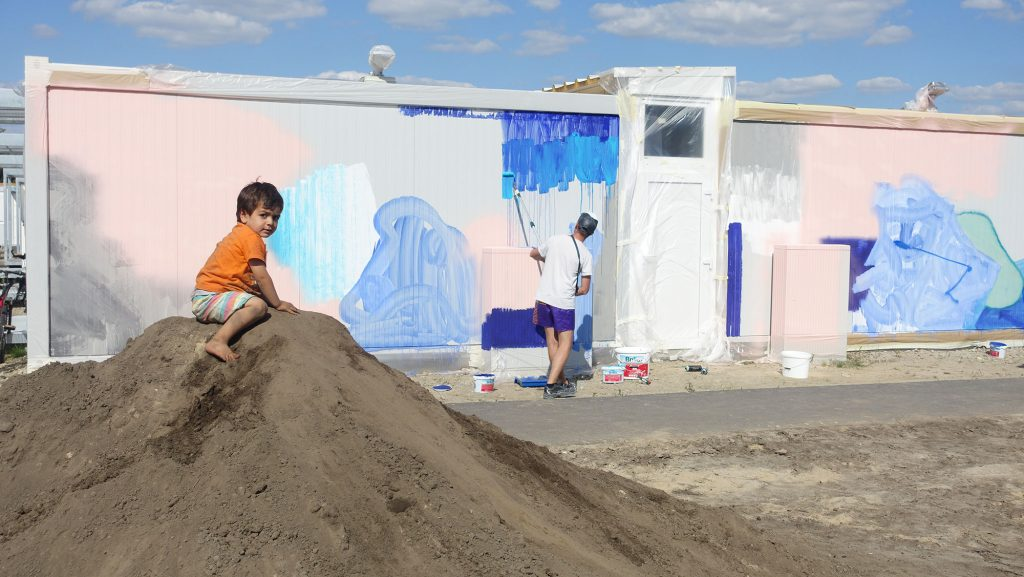 KLUB7 Christi painting in a refugee camp